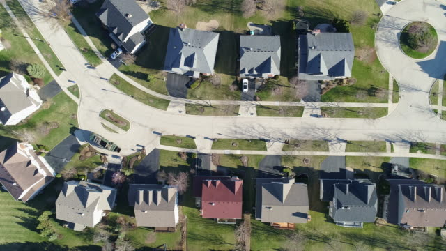 Top view directly above aerial view of the street in the residential neighborhood Libertyville, Vernon Hills, Chicago, Illinois. Cinematic drone video with the panning camera motion.