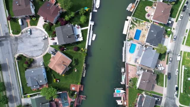 vídeos de stock, filmes e b-roll de vista superior, diretamente acima do vídeo drone de um canal em oceanside, nova york, com casas com piscinas em quintais e píeres com barcos ao longo da costa. olhando para a câmera com o movimento de panorâmica ao longo do canal. - marina