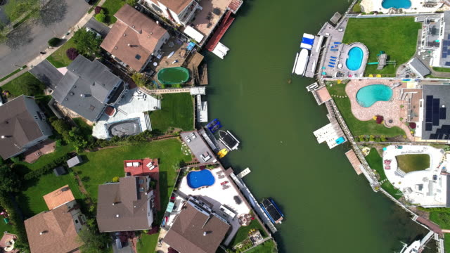 Top view, directly above drone video of a channel in Oceanside, New York City, with houses with pools on backyards and piers with boats along the shore. Spinning and descending combined camera motion.
