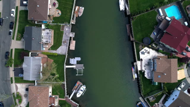 Top view, directly above drone video of a channel in Oceanside, New York City, with houses with pools on backyards and piers with boats along the shore. Looking down camera with the panning forward motion along the channel.