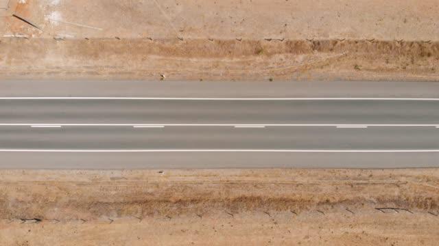 drone in alto girato sopra la stretta strada del deserto - in cima video stock e b–roll