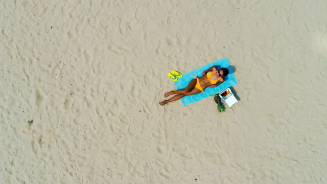 Top view drone shot of woman relaxing at the beach in summer Woman in bikini lying at the beach taking a sunbath relaxing on summer vacations, top view drone shot military private stock videos & royalty-free footage