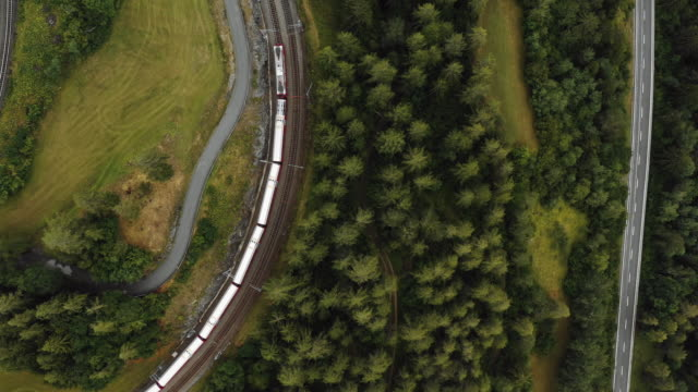 Top view, drone tracking epic red Glacier Express train cruising along peaceful summer Swiss Alps countryside villages.