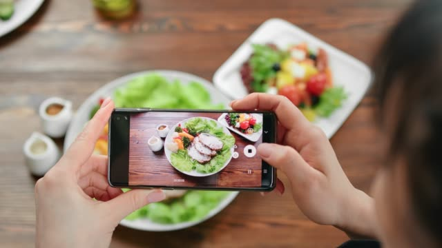 vídeos de stock e filmes b-roll de top view female taking photo of food on serving plate using smartphone. shot with red camera in 4k - meat plate