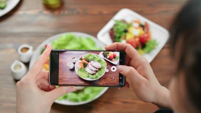 top view kvinnliga ta foto av mat på servering tallrik med smartphone. skjuten med röd kamera i 4k - sallad bildbanksvideor och videomaterial från bakom kulisserna