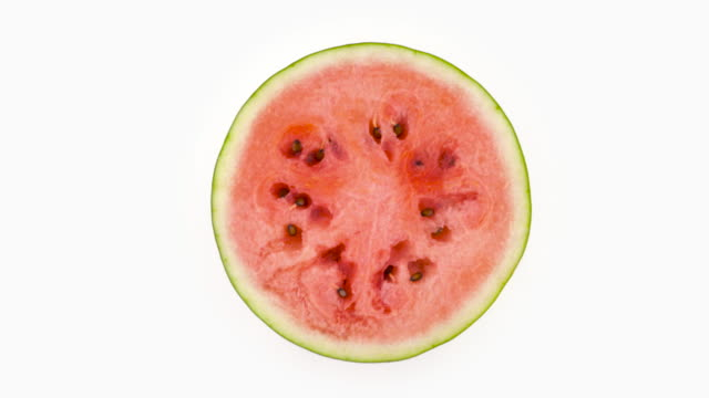 Top view from above of a half cut ripe watermelon slice. Cross section. Rotating on the turntable isolated on the white background. Close-up. Top view from above of a half cut ripe watermelon slice. Cross section. Rotating on the turntable isolated on the white background. Close-up. watermelon stock videos & royalty-free footage