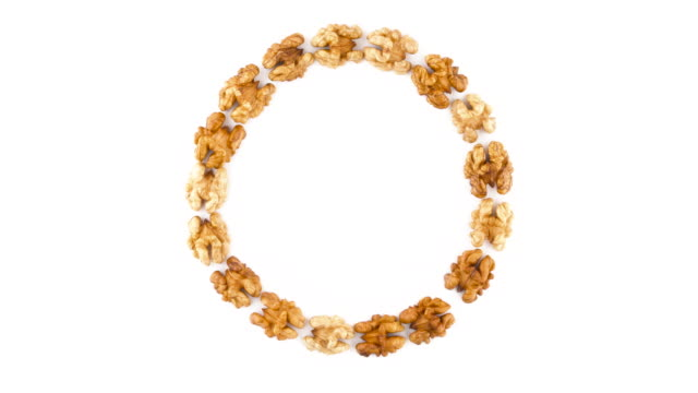 Top view from above of a large circle shaped walnuts without the shell. Rotating on the turntable isolated on the white background. Close-up. Macro.