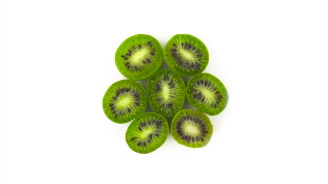 draufsicht von oben der kreis geformt mini kiwi hälften. langsam drehen auf die plattenteller. auf dem weißen hintergrund isoliert. close-up. makro. - tropischer cocktail stock-videos und b-roll-filmmaterial