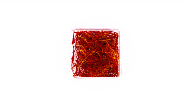 ovanifrån från ovan av transparent låda av hög kvalitet röd saffran trådar. långsamt roterande på skivtallriken isolerat på den vita bakgrunden. närbild. makro. - saffron on white bildbanksvideor och videomaterial från bakom kulisserna