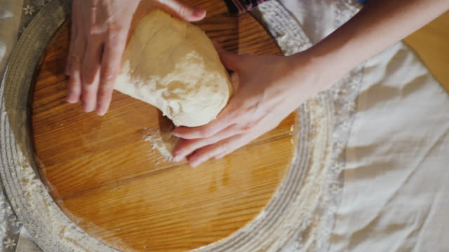 top view: hands knead the dough on a wooden board. the board is oiled with vegetable oil - nadziewany placek filmów i materiałów b-roll