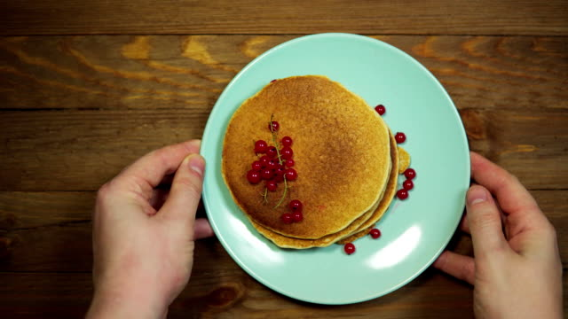 Top view hands put plate with pancakes and berries on wooden table, dolly shot. Top view of a hand putting a plate with appetizing pancakes and red currants on a wooden table, the camera is moving from left to right. table top view stock videos & royalty-free footage