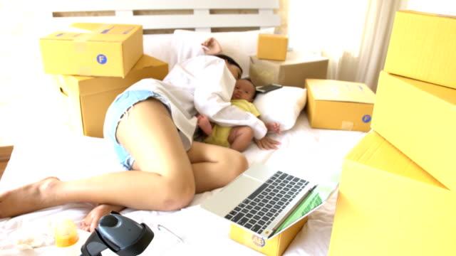 ovanifrån: hennes son om fastställande enligt omfamnande av ung vacker kvinna, men hon tupplur - working from home bildbanksvideor och videomaterial från bakom kulisserna
