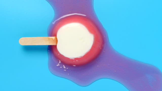 top view honey peach shape and flavor popsicle melting on a blue background timelapse - vídeo