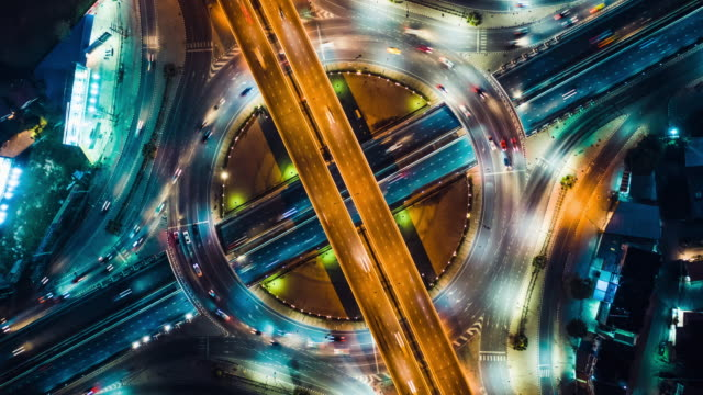Top view hyperlapse time-lapse of car traffic at circle roundabout, 4K UHD drone zoom out aerial shot. Land transportation, urban cityscape, or advanced transport technology concept