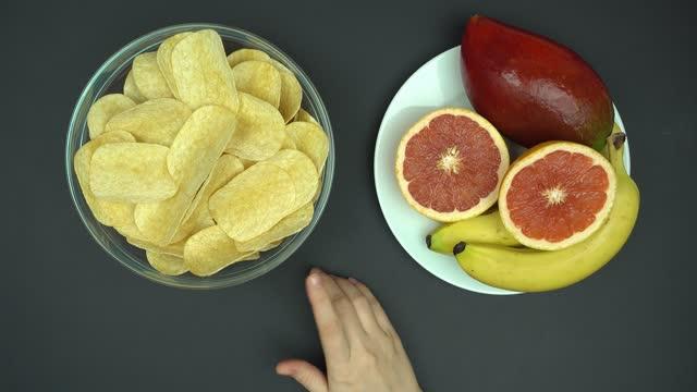 top view lång tänkande och göra rätt val mellan hälsosam och skräpmat. - fett näringsämne bildbanksvideor och videomaterial från bakom kulisserna