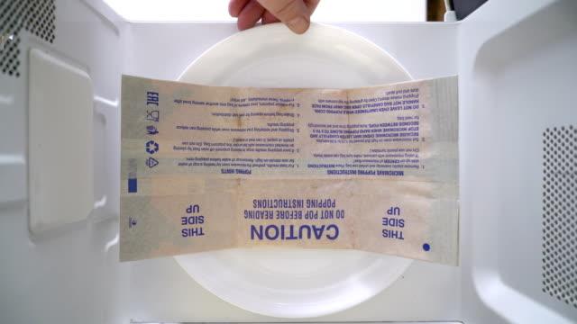 stockvideo's en b-roll-footage met bovenaanzicht popcorn maken in een papieren zak in de magnetron - popcorn