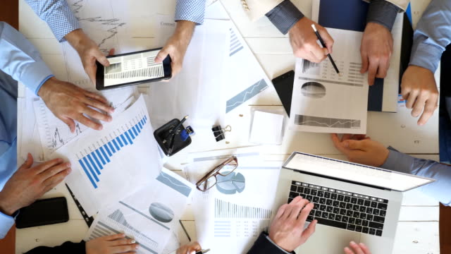 Top view male and female hands of business people planning strategy for corporate project in office. Business team checks financial graphs at desk. Colleagues sitting at table and examining documents.