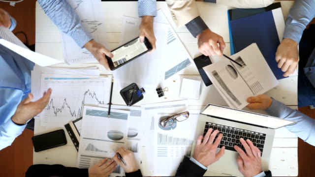Top view male and female hands of business people planning strategy for corporate project in office. Business team sitting at table and checking financial graphs. Coworkers examining documents at desk.