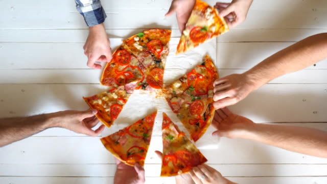 vídeos de stock e filmes b-roll de top view male and female hands taking slices of pizza with cheese, tomatoes and ham from food delivery. group of hungry friends sitting at desk and sharing delicious lunch on wooden table background. - pizza