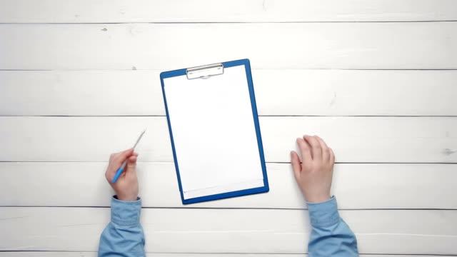 vidéos et rushes de vue de dessus masculin mains tenant crayon couché au comptoir avec le presse-papier avec du papier par dessus l'espace copie - bloc note