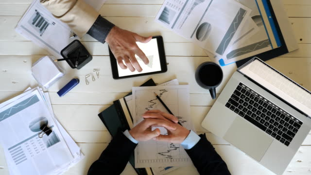 Top view male hands of two coworkers checking graphs with statistics and discussing financial reports in office. Successful businessmen sitting at wooden table and developing a new business project.