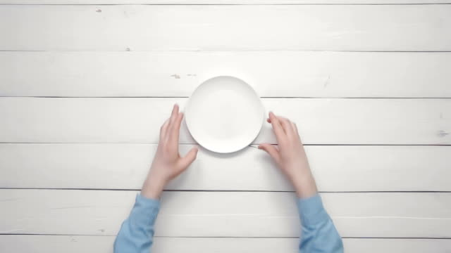 Top view male hands putting white plate and silverware on white desk from above copy space