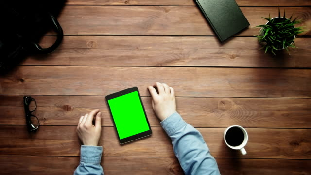 Top view male hands working with big data graphs and charts on smartphone and digital tablet with green screen lying on white desk from above video