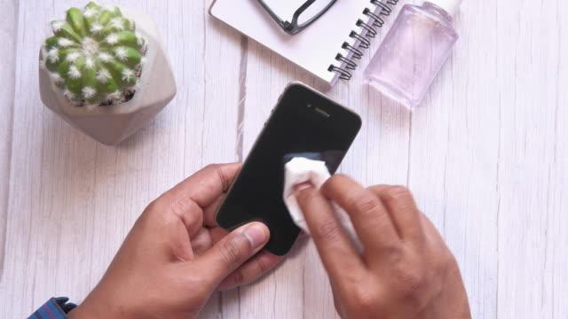 top view man rengöring smart telefon eller förebyggande av sjukdomar - resistance bacteria bildbanksvideor och videomaterial från bakom kulisserna
