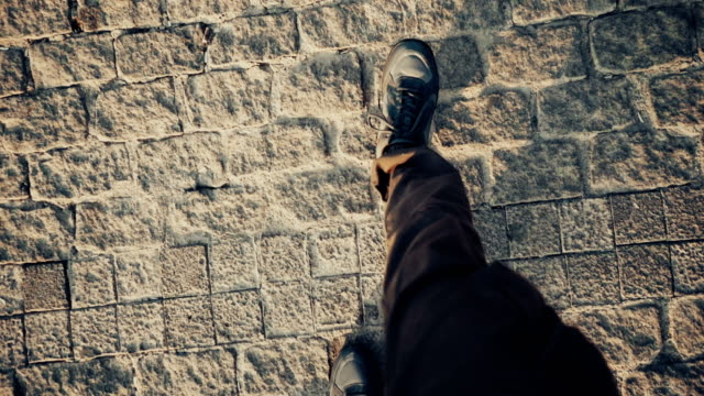 Top view POV of man in shoes walking at historical ancient sidewalk video