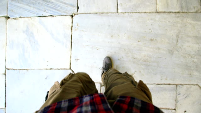 Top view POV of man in sneakers walking historical ancient sidewalk video