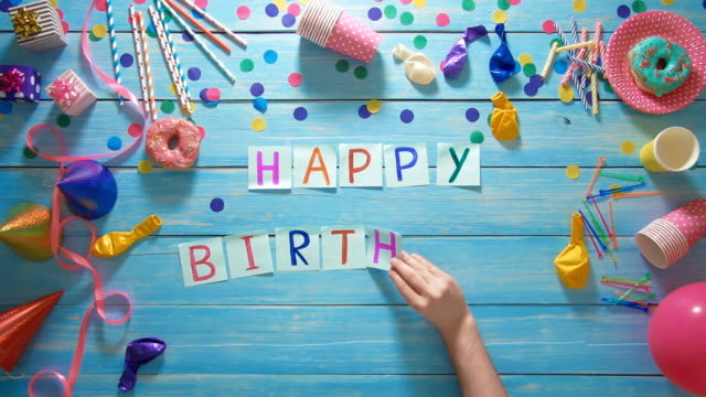 Top view man puts words Happy Birthday on the table with birthday decoration video