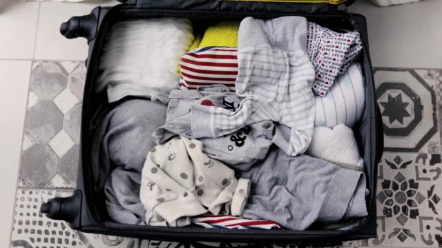 vídeos y material grabado en eventos de stock de packs mamá bebé cosas en la maleta de la vista superior - viajes familiares