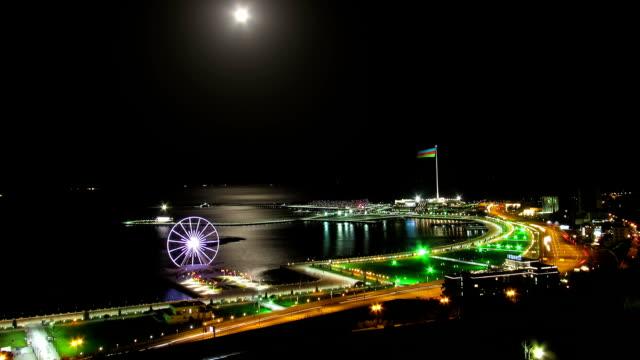 vista dall'alto di una grande città di notte, ruota panoramica sullo sfondo del mare e del sentiero lunare. traffico sulle strade. accelleratore - full hd format video stock e b–roll