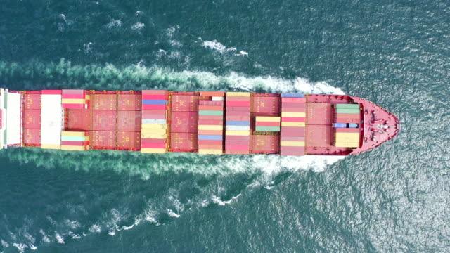 top view of a cargo ship sailing at sea - sezione superiore video stock e b–roll