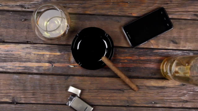 vídeos de stock e filmes b-roll de top view of a cigar on an ashtray, a glass of alcohol and lighter next to a bottle of alcohol. crane shot. - top view, dark wood table, empty