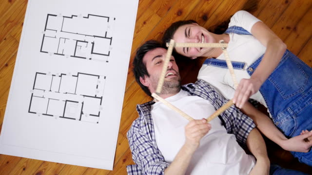 top view of a couple in love lying on the ground, who wants to buy the new house, they travel with the imagination on how they will be in a future and dream of a new house. - key ring stock videos & royalty-free footage