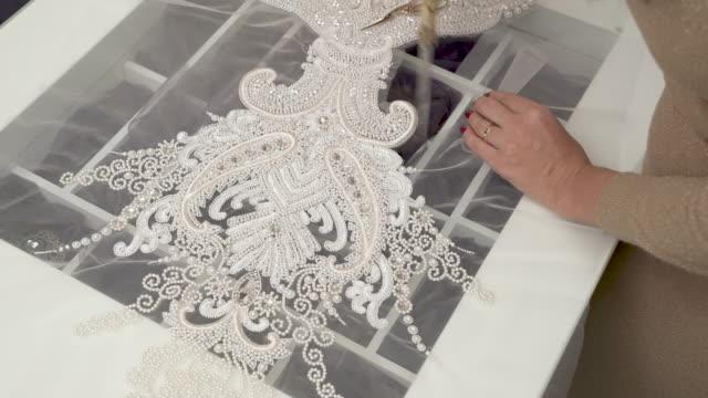 vídeos de stock, filmes e b-roll de uma vista superior de um desenhador cortar o laço lantejoulas e frisado com uma tesoura grande e, em seguida, com a tesoura menor - moda de casamento