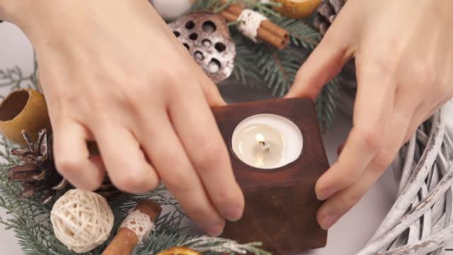 top-ansicht einer weiblichen hand, die brennende kerze auf den geschmückten adventskranz legt. weihnachtstraditionen konzept.mov - advent stock-videos und b-roll-filmmaterial