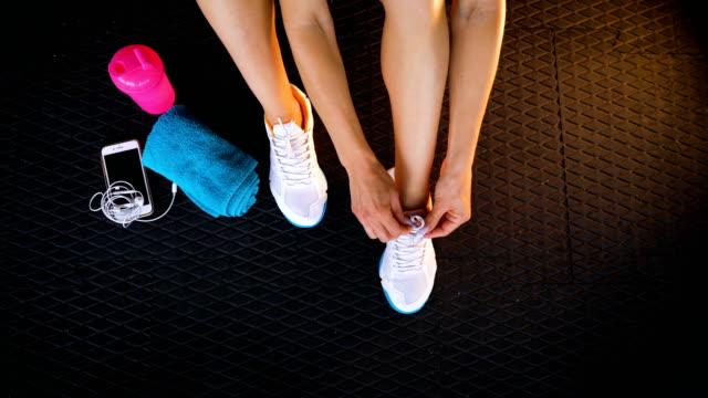 スニーカーの靴ひもを結ぶことジムの床の上に座ってフィット女性の平面図です。 - 女性選手点の映像素材/bロール