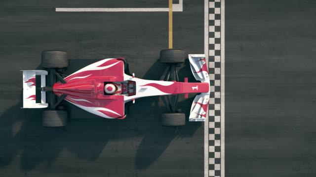 stockvideo's en b-roll-footage met bovenaanzicht van een formula one race auto rijden over finishlijn in slow motion - winnen