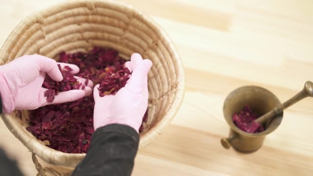Top view of a girl's hands, she carefully sorts dried rose petals in basket. There is a copper mortar with pestle on the table. Top view of a woman's hands, she carefully sorts dried rose petals in basket. There is a copper mortar with pestle on the table. mortar and pestle stock videos & royalty-free footage