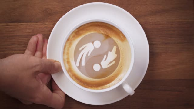 Top view of a hand serving coffee with male female yin yang latte art