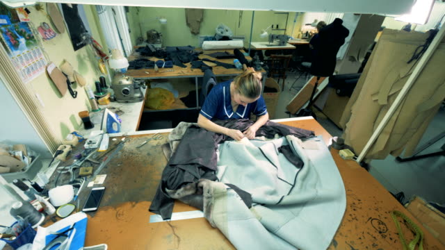 top view of a leather coat getting sewn by a female specialist - sarta video stock e b–roll