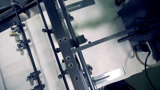 top view of a machine tool relocating multiple pieces of paper one by one - завод по переработке пищевых продуктов стоковые видео и кадры b-roll