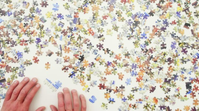 Top view of a man doing a jigsaw puzzle