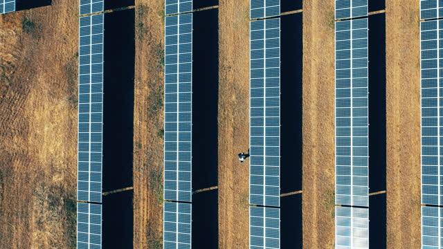 Top view of a repairman walking among solar panels video