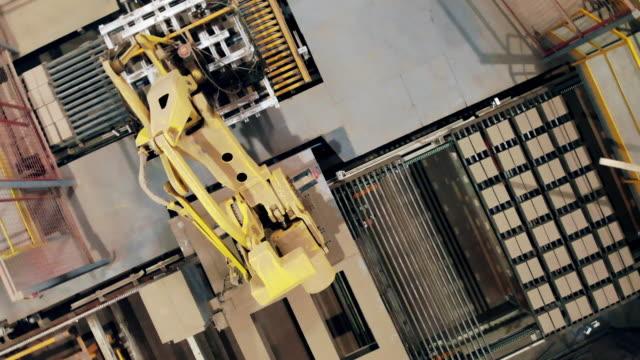 vídeos de stock e filmes b-roll de top view of a robotic arm relocating bricks from the conveyor - braço