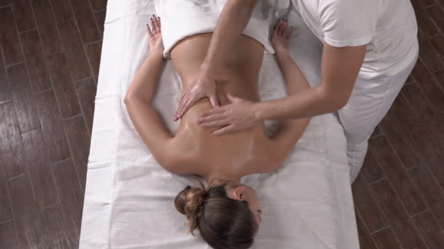 vídeos de stock e filmes b-roll de top view of a skillful therapist performing back massage to a client at spa. body care concept. approaching camera shot - massajar
