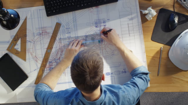 Top View of a Technical Engineer Working on His Blueprints, Drawing on Plans. Various Drawing Objects Lying on his Table. video