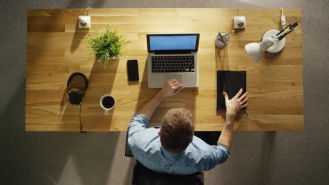 vídeos y material grabado en eventos de stock de vista superior de todo un día laborable de un diseñador creativo. trabajando en su computadora de escritorio, bebiendo café, yendo a almorzar, escribiendo cosas en su cuaderno. - escritorio